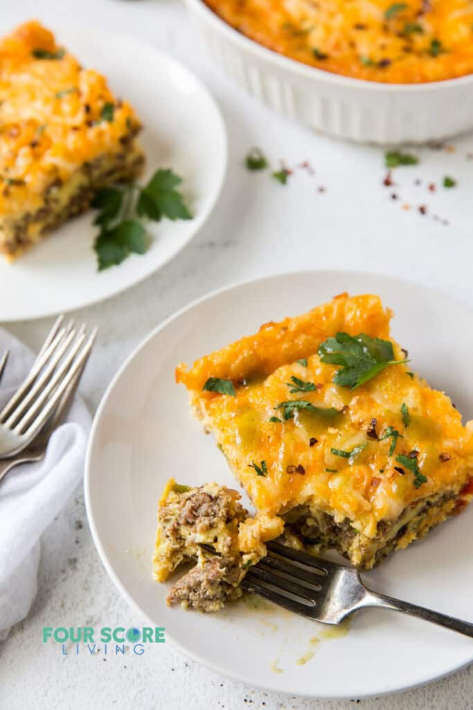 a square of breakfast casserole on a plate being eaten with a fork