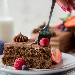 a slice of chocolate cake being eaten with a fork held by a feminine hand with red nail polish.