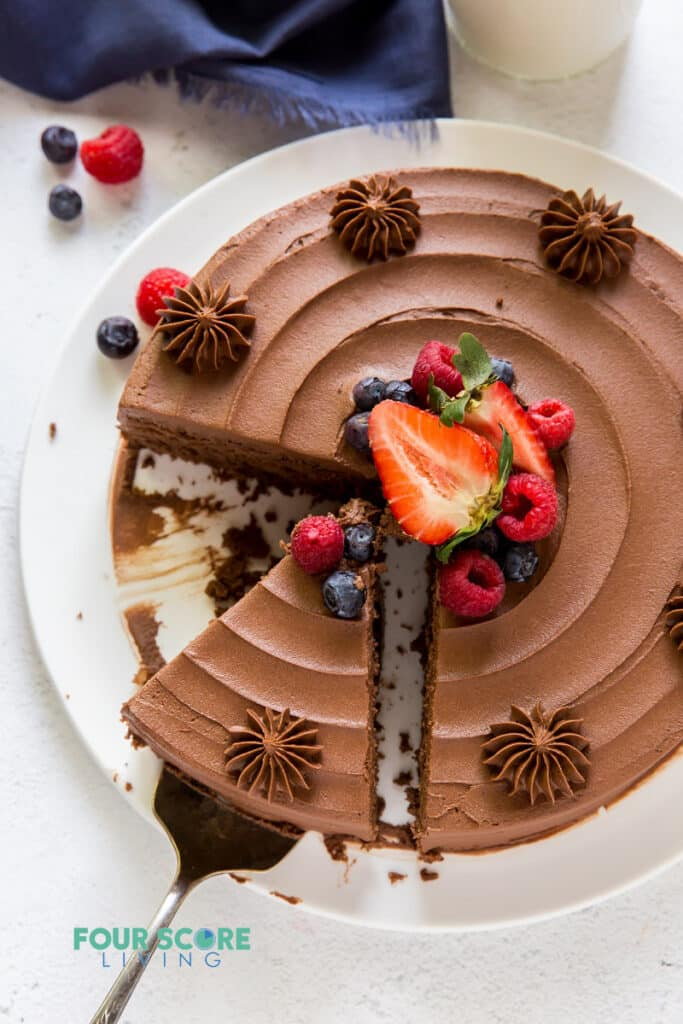 Top down view of a chocolate cake with a slice removed and berries in the center.