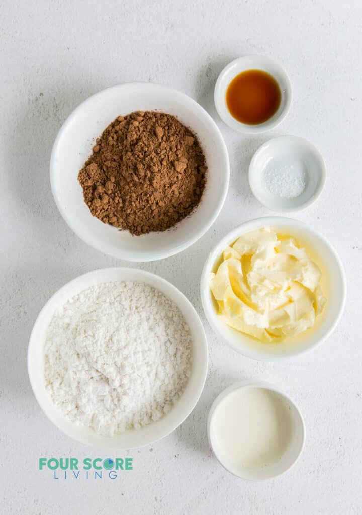 All of the ingredients for keto chocolate frosting in small white bowls. Ingredients include butter, cocoa, sweetener, cream, vanilla.