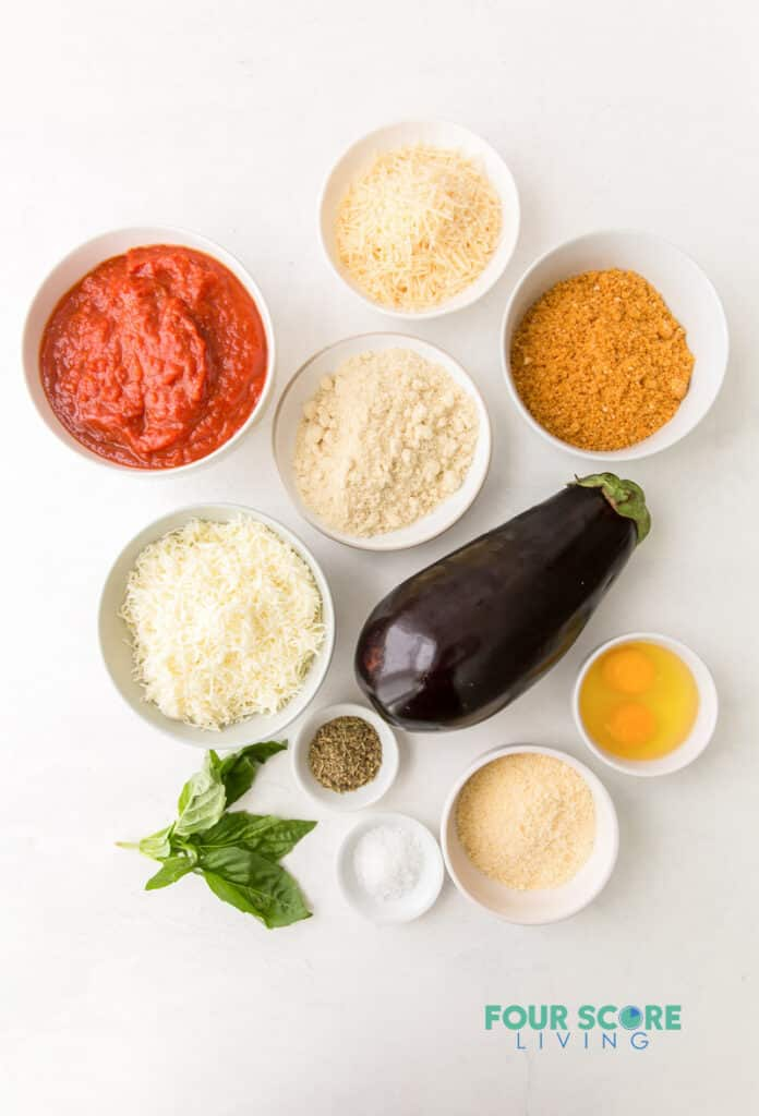 top down view of ingredients for eggplant parmesan, including sauce, seasonings, cheeses, eggplant, and eggs.