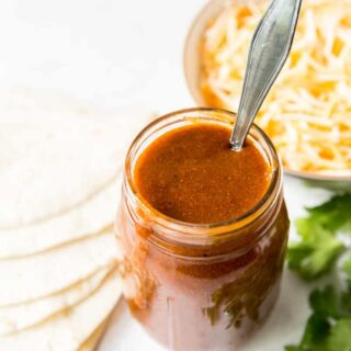 a jar of enchilada sauce with a spoon it in, next to a bowl of cheese, a stack of tortillas and some cilantro.