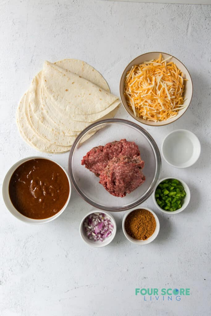 top down view of ingredients for keto enchiladas, including tortillas, cheese, meat, sauce, and seasonings.