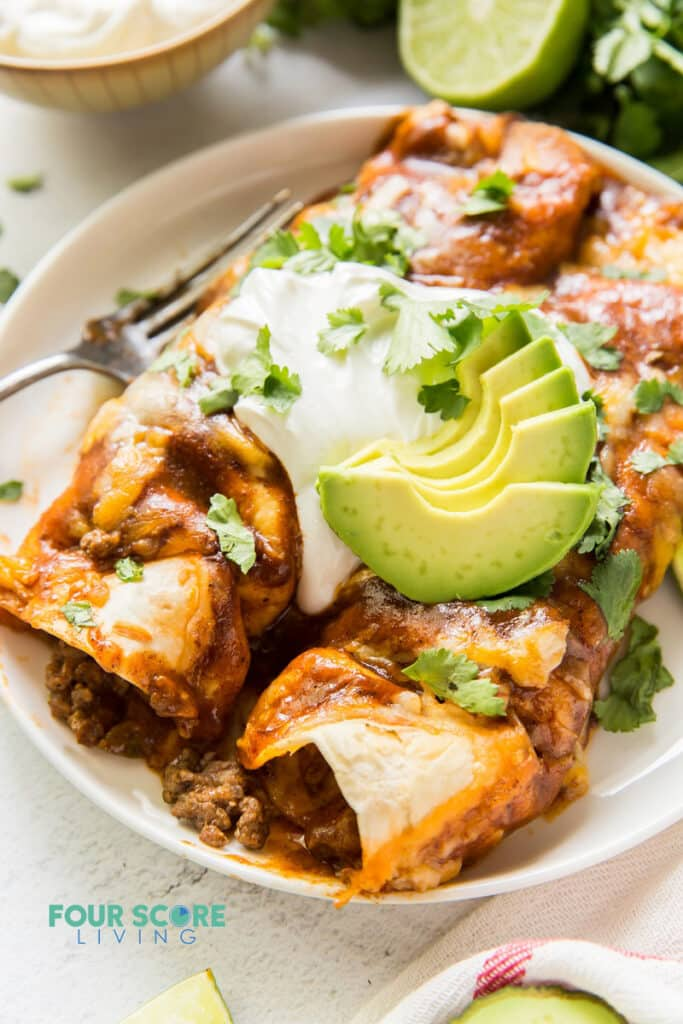 Closeup view of two enchiladas on a plate topped with sour cream, avocado, and cilantro.