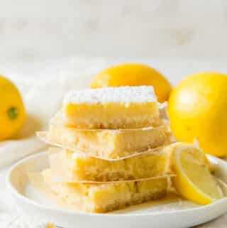 a plate of 4 leman bars, stacked on top of each other, surrounded by lemons.