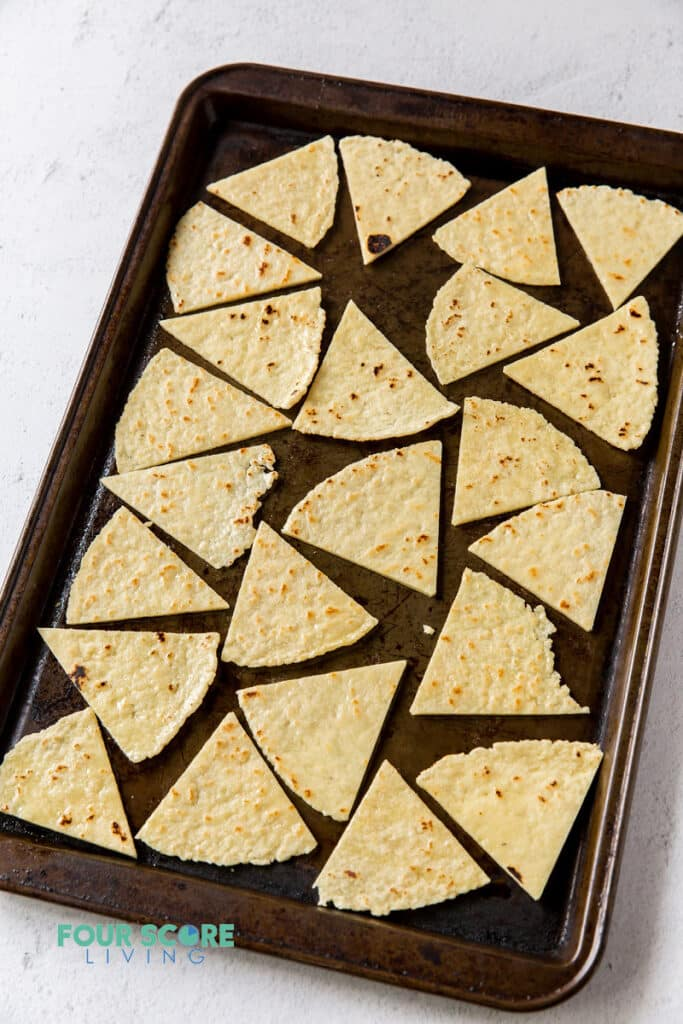a sheet pan filled with tortilla triangles.