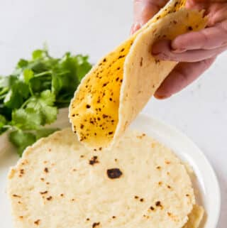 A hand folding a tortilla over a plate of tortillas.
