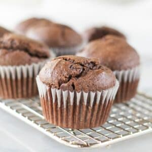 a keto chocolate muffin on a wire cooling rack in front of other muffins