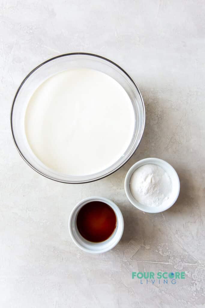 Ingredients for keto ice cream in separate bowls, including cream, sweetener, vanilla.