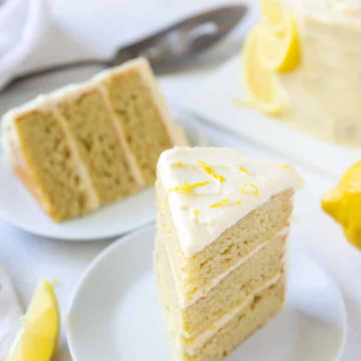 Two plates each with a three layer slice of lemon cake.