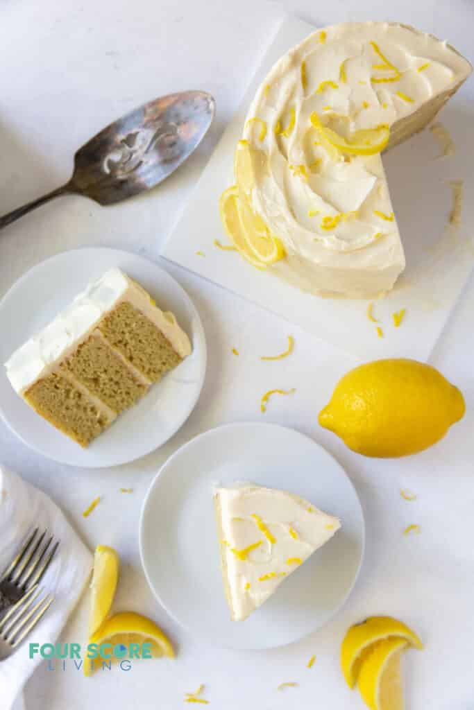 top down view of a lemon cake being served, and two plated slices of cake. Lemons and lemon slices garnish the cake.