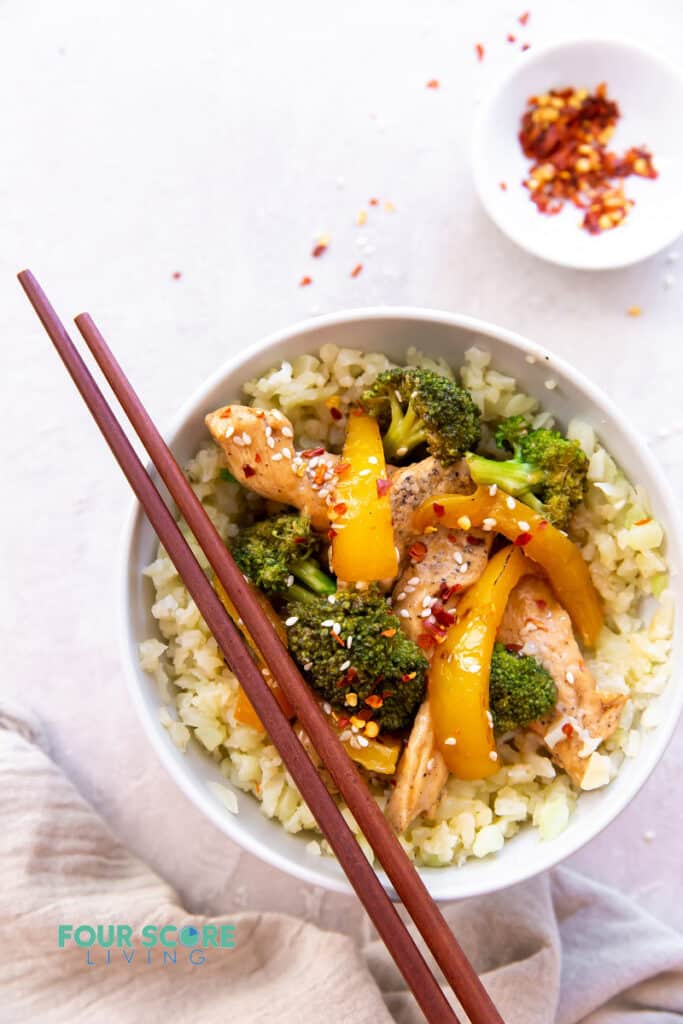 a bowl of stir fry over rice with chopsticks on top