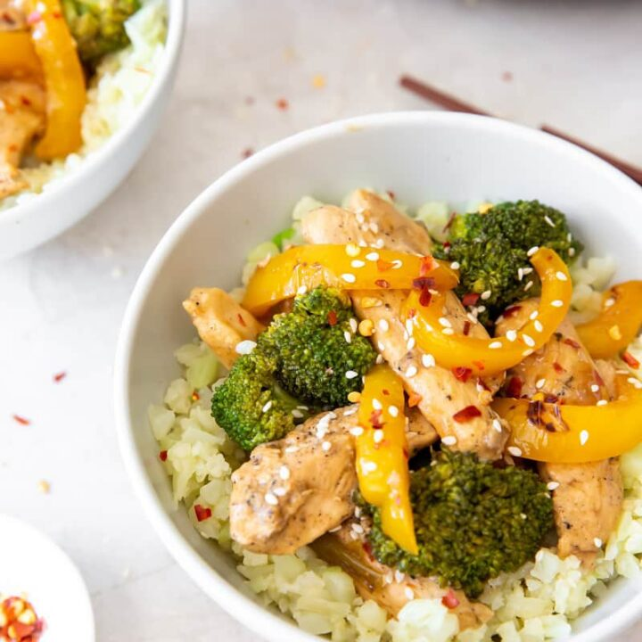 a bowl of chicken, broccoli, and pepper stir fry on top of cauliflower rice.