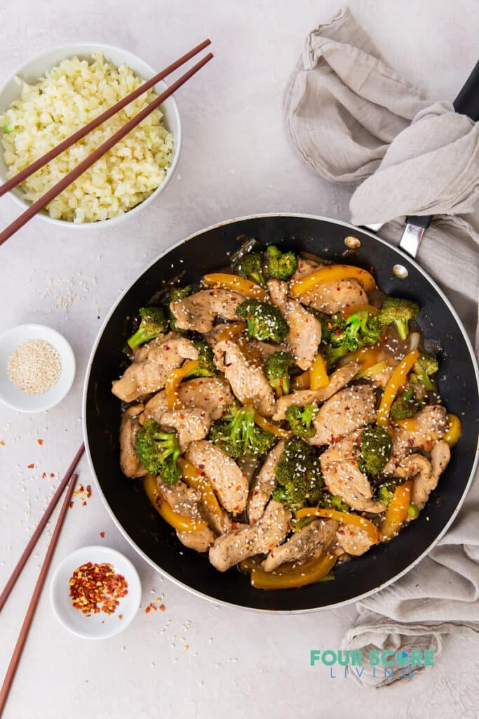 top down view of a chicken and broccoli stir fry in a frying pan, surrounded by chopsticks, rice, and garshishes.