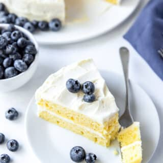 a slice of vanilla layer cake on a plate with a bit being taken. Cake is topped with blueberries.