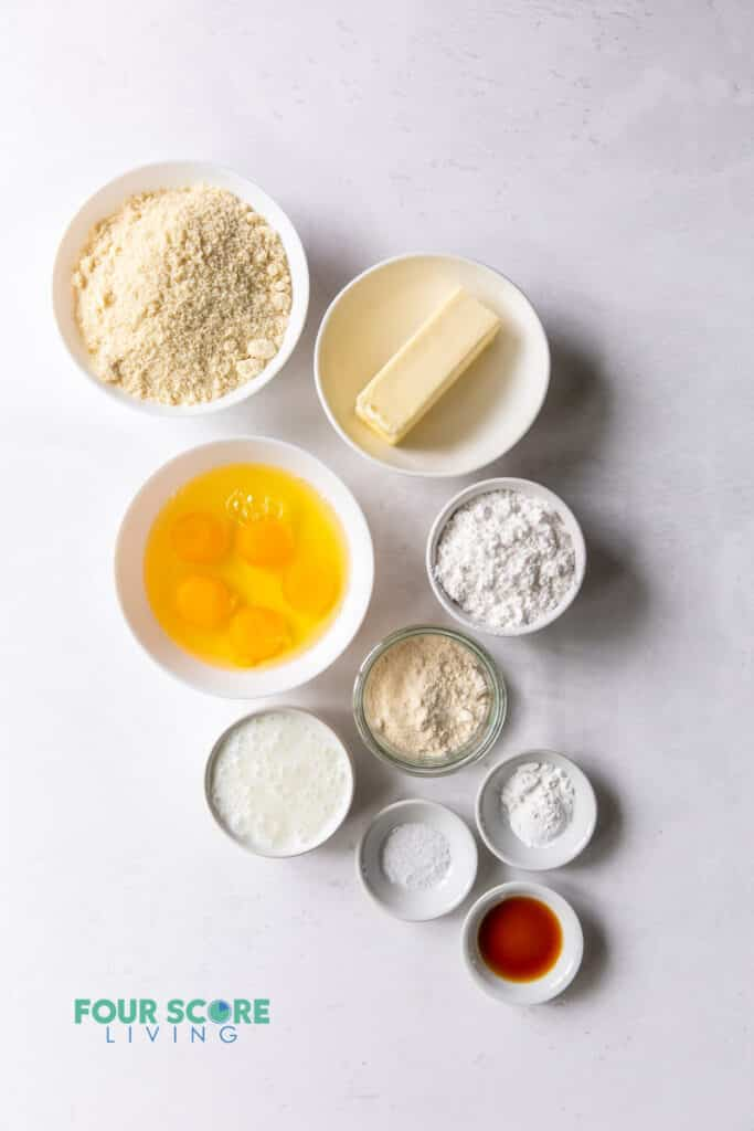 Top down view of ingredients for keto vanilla cake including eggs, flours, butter, and others.