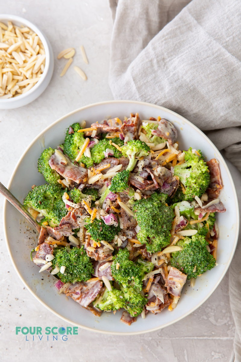 a large white bowl filled with broccoli salad with cheese and bacon