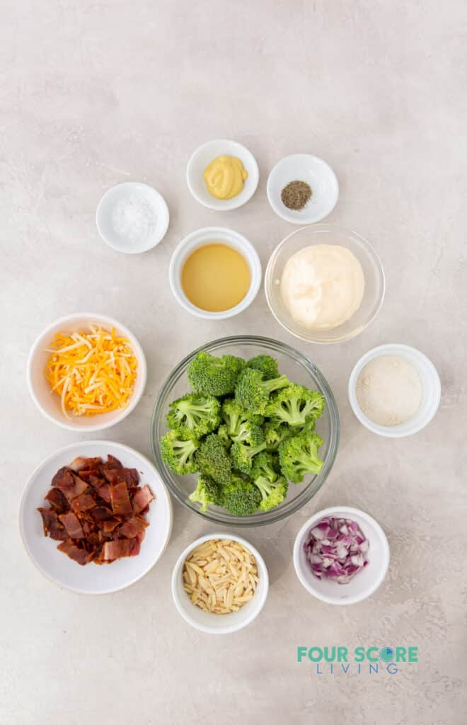 top down view of the ingredients needed to make keto broccoli salad including broccoli, cheese, onion, seasonings, and mayonnaise