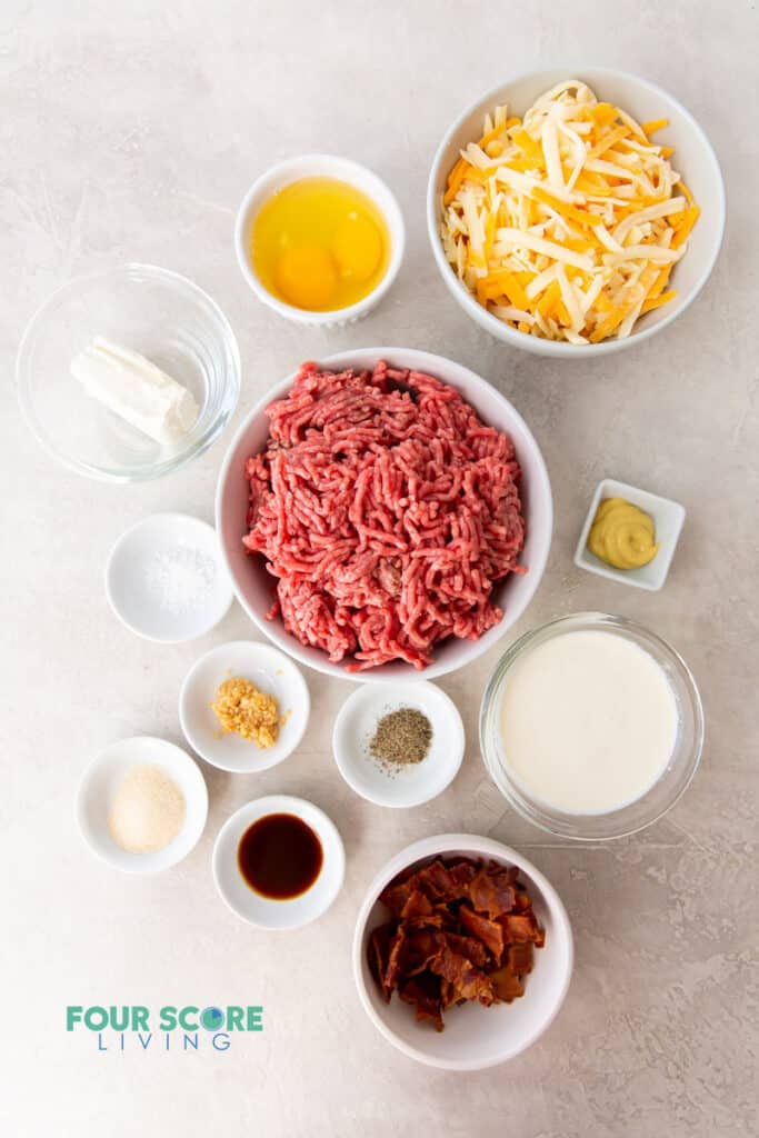 top down view of the ingredients needed for cheeseburger casserole, all in separate dishes. Includes hamburger meat, cheese, eggs, bacon, and seasonings