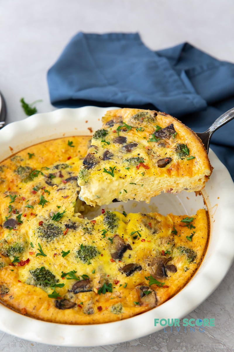 a white ceramic pie pan of quiche with broccoli and mushrooms, one wedge is being lifted out.