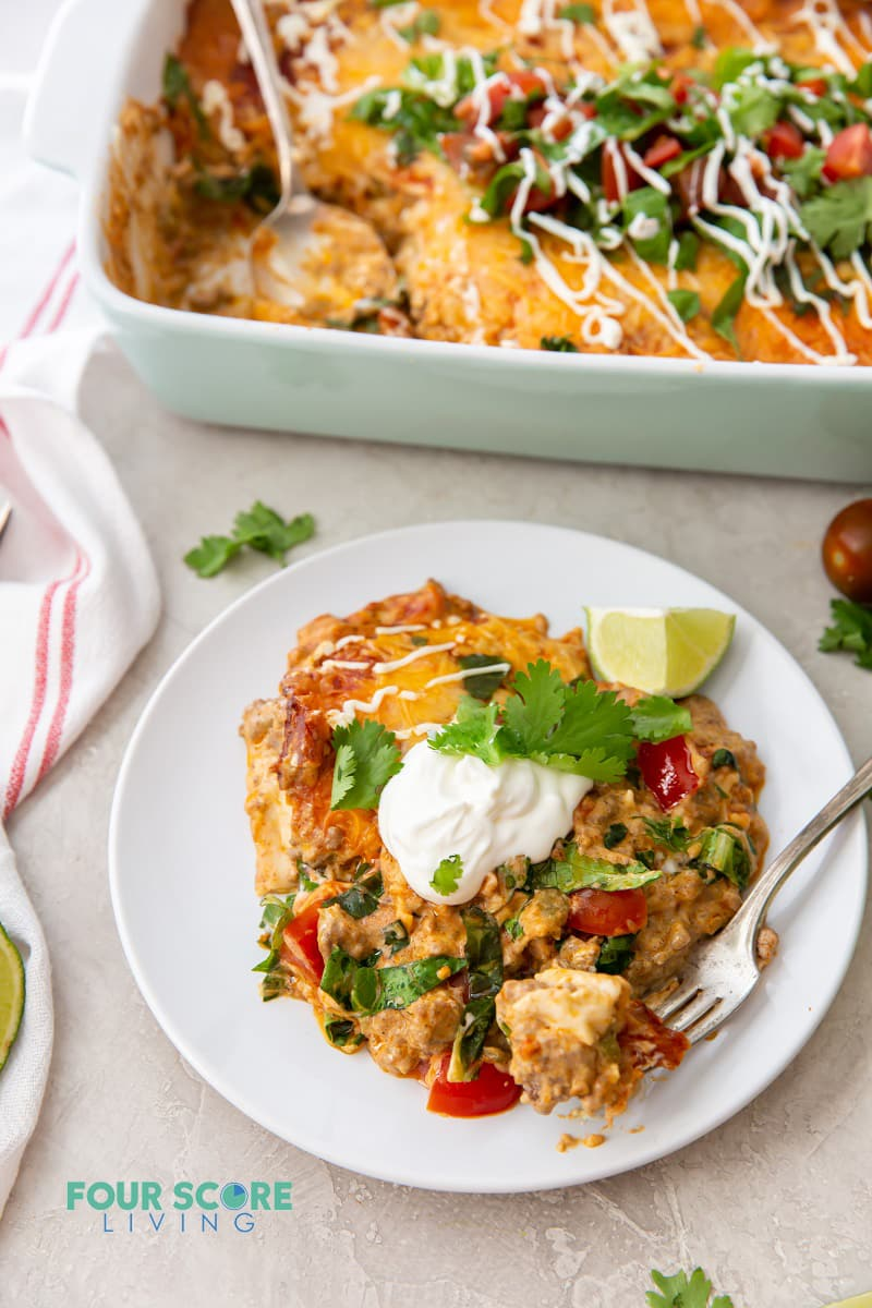 a plate of keto taco casserole topped with sour cream and cilantro, next to a casserole dish full of the same.