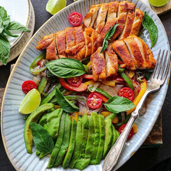 sliced keto chicken fajita meat on a white plate with avocado, onions, tomato