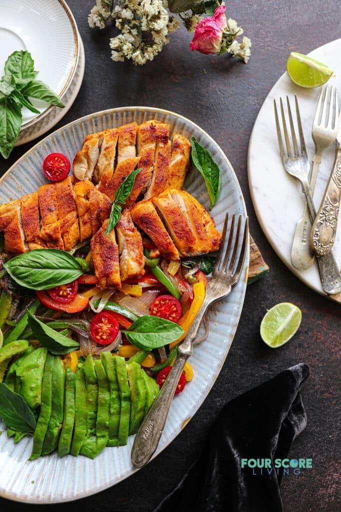 sliced keto chicken fajita meat on a white plate with avocado